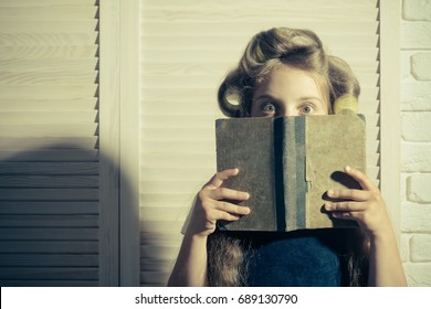 Little baby with book. Child in school. Education and childhood. Small girl with curler in hair.