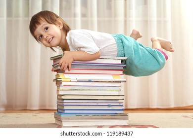 Little baby with a book on a light