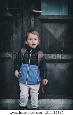 741b1cee6aa Little baby boy with a backpack standing at the old big door on his first  day