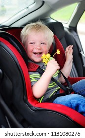 little baby boy with blond hair sitting in a red car seat and smiling