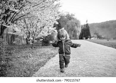 Little baby boy in the blossom garden. Spring