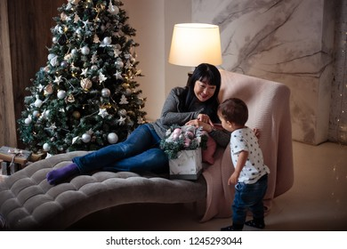 Little baby boy in a casual jacket and jeans sitting near christmas tree with his grandmother