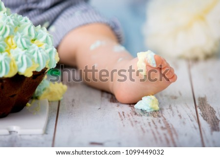Little baby boy, celebrating his first birthday with smash cake party, studio isolated shot on blue background