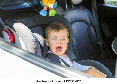 Little baby boy is crying in his car seat not willing to sit in it. Traveling with child and baby safety concept. Little passenger transportation