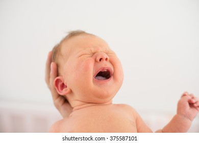 little baby boy crying in his mother's arms. He is not yet one month old