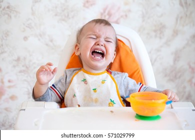 Little baby boy crying and screaming during eating, sitting in highchair