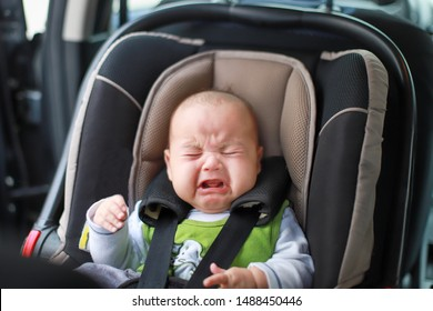Little baby boy is crying while fastened in safety car seat. Asian child 3 months old traveling by car