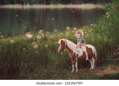 Little baby boy with curly hair dressed as hobbit sitting on a piebald pony horse on the lakeshore