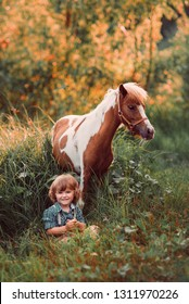 Little baby boy with curly hair dressed as hobbit playing with piebald pony horse in summer forest