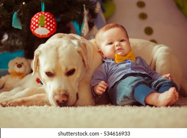 Little baby boy with  dog lying on the floor