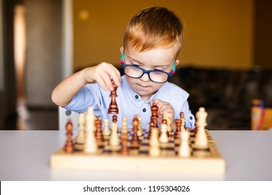 Little baby boy with down syndrome with big blue glasses playing chess in kindergarten