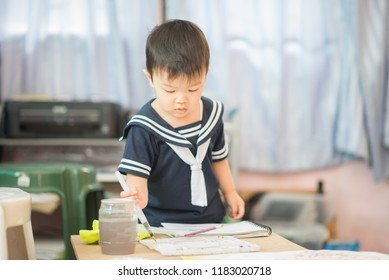 Little baby boy drawing picture water coloring