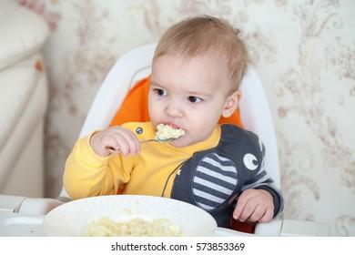 Little baby boy eating sitting in highchair