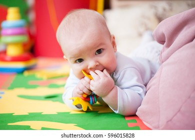 Little baby boy eats, teething and hungry, chewing toy