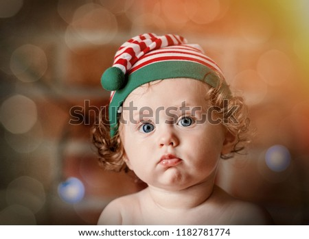 c604217e57f8e Little baby boy in elf hat with Christmas fairy lights on background. Christmas  time season