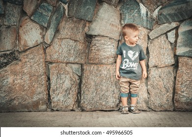 Little baby boy in fashionable clothing have fun outdoors