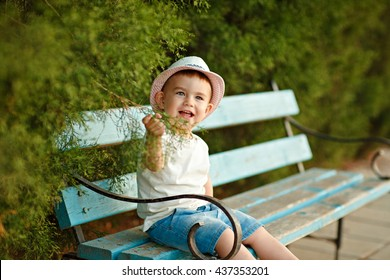 Little baby boy in a hat sitting on a bench and smiling in the summer