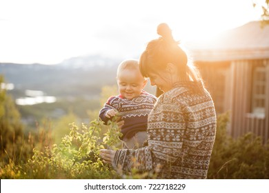 Little baby boy with her young mother having fun outside in the countryside in Norway in the National park Hardangervidda at sunset with warm red light. Blurred background.