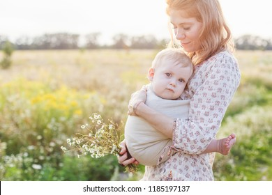Little baby boy and his mother walking in the fields. Mother is holding and tickling her baby, babywearing in sling