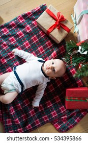 Little baby boy lying under Christmas tree among presents