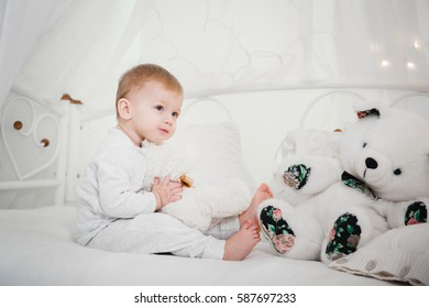 little baby boy in pajamas on the bed having fun