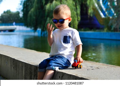 little baby boy playing with a dump truck in colored sunglasses and a white T shirt in the park