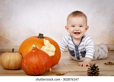Little baby boy with pumpkins