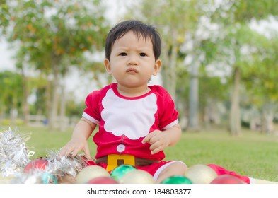 Little Baby Boy with Santa Claus suit in the Garden.