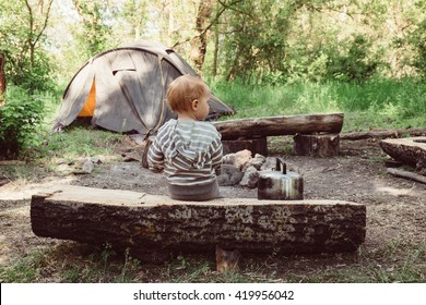 Little baby boy sitting at camping place on wood near campfire and tent. Tent, campfire on campsite outdoors. Travel, camping and adventure with child. Kid sitting at campsite. Little traveler.