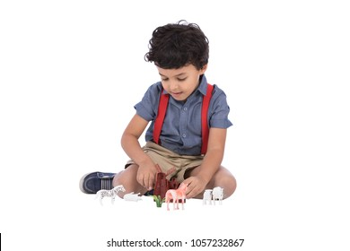 A little baby boy sitting on the floor playing with plastic animals, isolated on a white background.