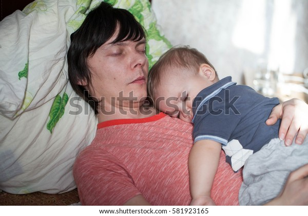 Little baby boy sleeping in bed with parents, with the father