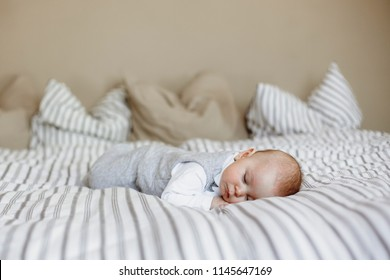 Little baby boy, sleeping in big bed in bedroom in the afternoon