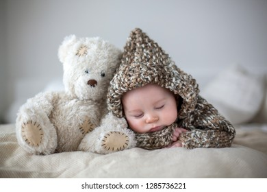 Little baby boy , sleeping at home with soft teddy bear toys, lying down