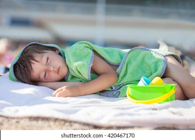 Little baby boy, sleeping on the beach in the afternoon wrapped in towel