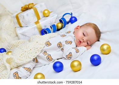 Little baby boy sleeping in pajamas with a knitted plaid on the background of gift boxes and colored balls.