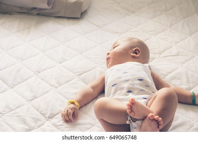 Little baby boy sleeping in white bedroom at home.