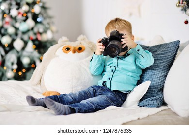 little baby boy with a SLR camera on the background of a Christmas decor