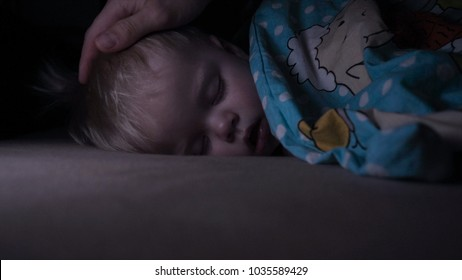 Little baby boy sweetly sleeps in bed, dad puts his son to bed.