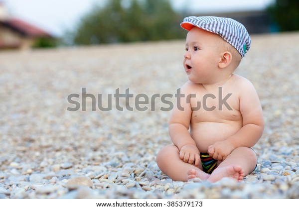 Little baby boy in swimming trunks sitting on beach pebbles