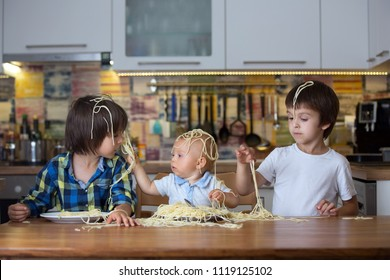 Little baby boy, toddler child and his older brothers, eating spaghetti for lunch and making a mess at home in kitchen