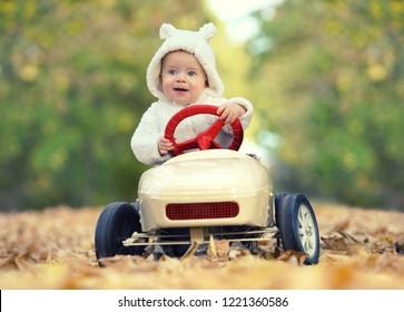 little baby boy in toy car in autumn park