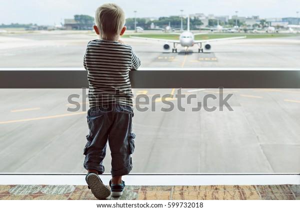 Menino bebê esperando embarque para o vôo no salão de trânsito do aeroporto e olhando através da janela no avião perto do portão de partida. Estilo de vida familiar ativo, viajar de avião com criança em férias de verão