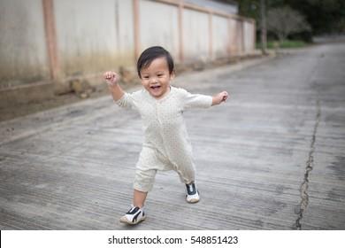 Little baby boy walking along the street.