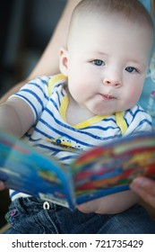 Little Baby Child Boy Six Months Old is Reading