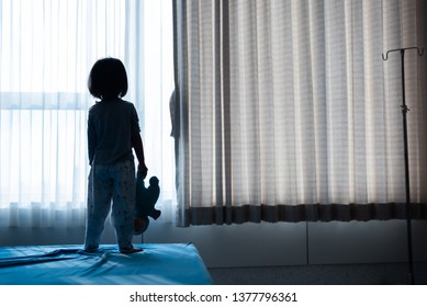 Little baby child sitting on bed playing with the doll in the dark room with light throught curtain
