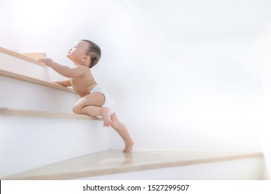 Little baby climbing up stairs at home.The concept development adorable baby nine months.