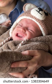 little baby crying in the arms of his mother, newborn colic
