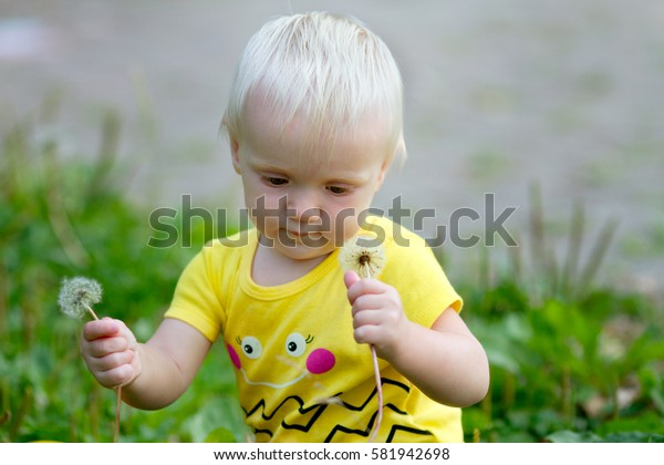 Little baby with dandelions in the park