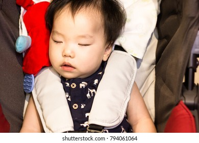 A little baby is deep sleeping in the stroller. Close up.