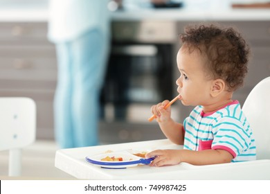Little baby eating puree indoors